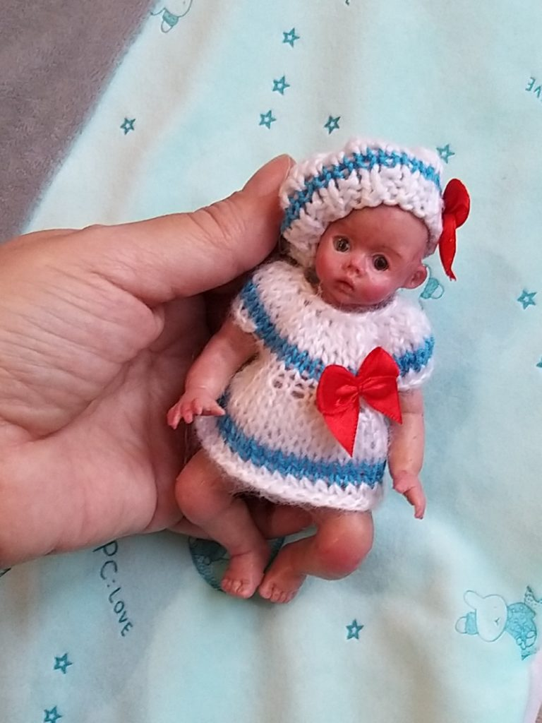 Miniature silicone girl in a marine suit knitted handmade